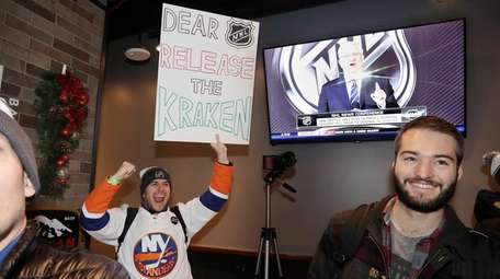 Max Rubin cheers and holds a sign in