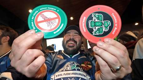 Otto Rogers playfully holds up stickers against the