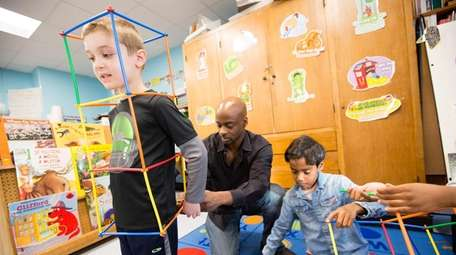 Michael Gittens, center, helps Evan Frank and Asif