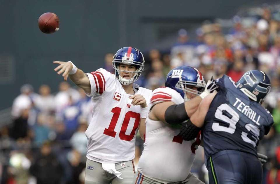 Giants quarterback Eli Manning throws as teammate Chris