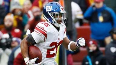 Giants running back Saquon Barkley runs away from