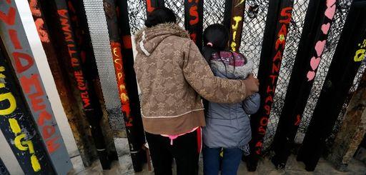 A Honduran migrant and her daughter peer through