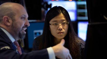 Stock traders James Denaro, left, and Vera Liu