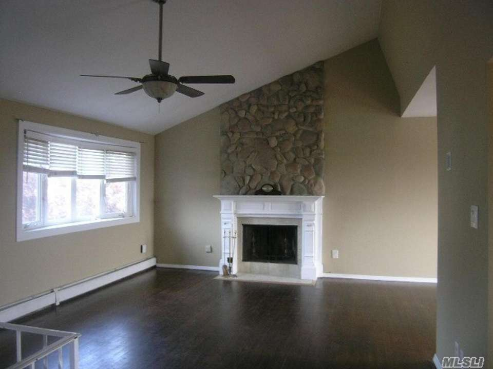 The living room features cathedral ceilings and a