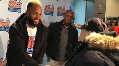 Mets shortstop Amed Rosario greets a fan who