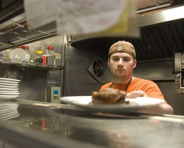 Chef Eric Lomando expedites dishes on a busy