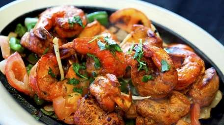 Shrimp and lamb kebabs are served on a