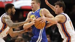 Golden State Warriors' David Lee, center, protects the