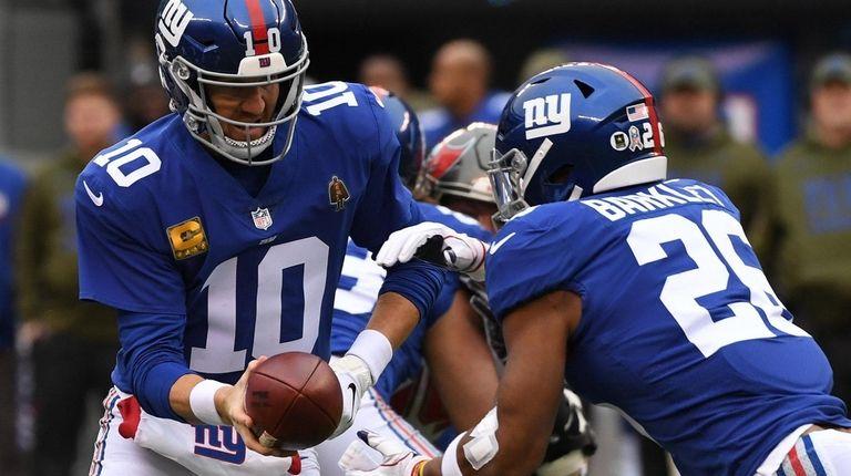 Giants quarterback Eli Manning hands the ball off