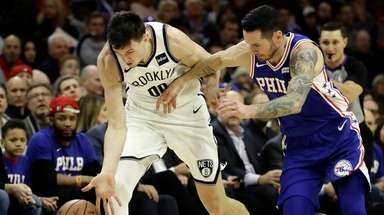 Nets' Rodions Kurucs, left, and Philadelphia 76ers' JJ
