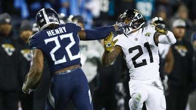Derrick Henry of the Titans fends off defender