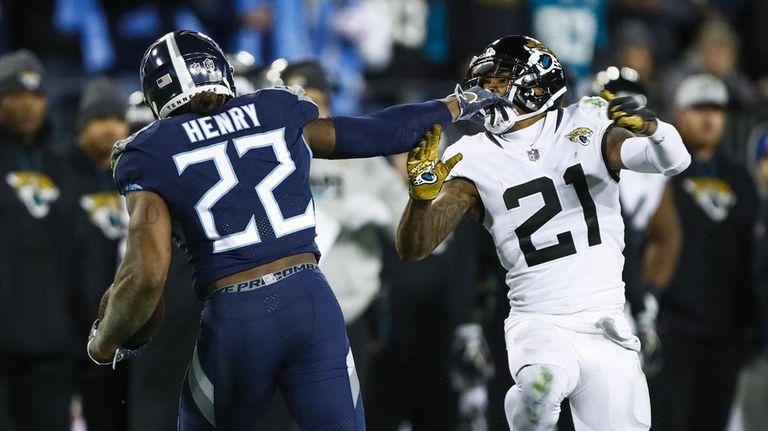 Derrick Henry of the Titans fends off defender