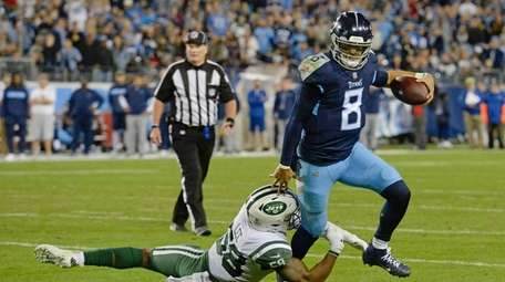 Tennessee Titans quarterback Marcus Mariota gets out of