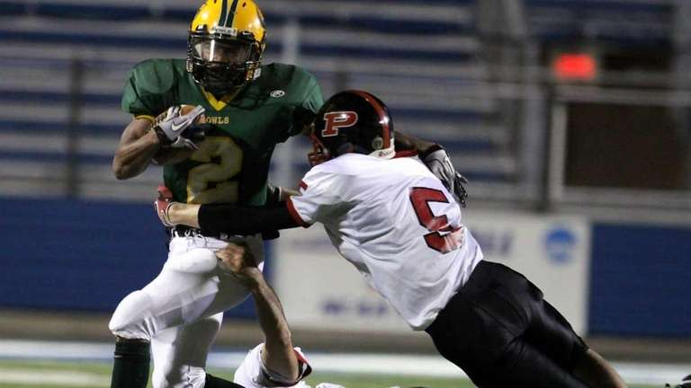 Carrying a few Plainedge defenders is Lynbrook's Travis