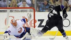 New York Islanders goalie Dwayne Roloson, left, stops