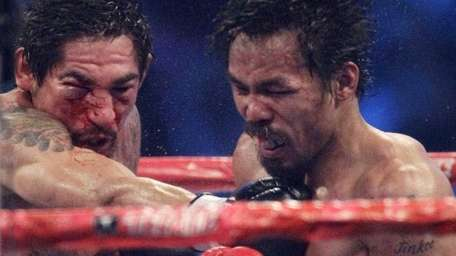 Manny Pacquiao, right, and Antonio Margarito, left, exchange