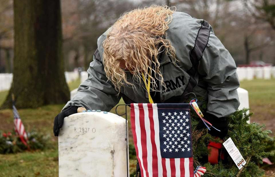 People lay wreaths on the graves of fallen