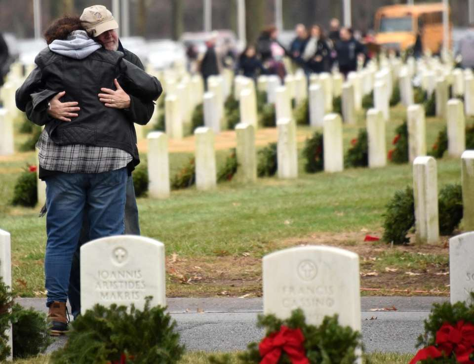 People embrace as wreaths are laid on the
