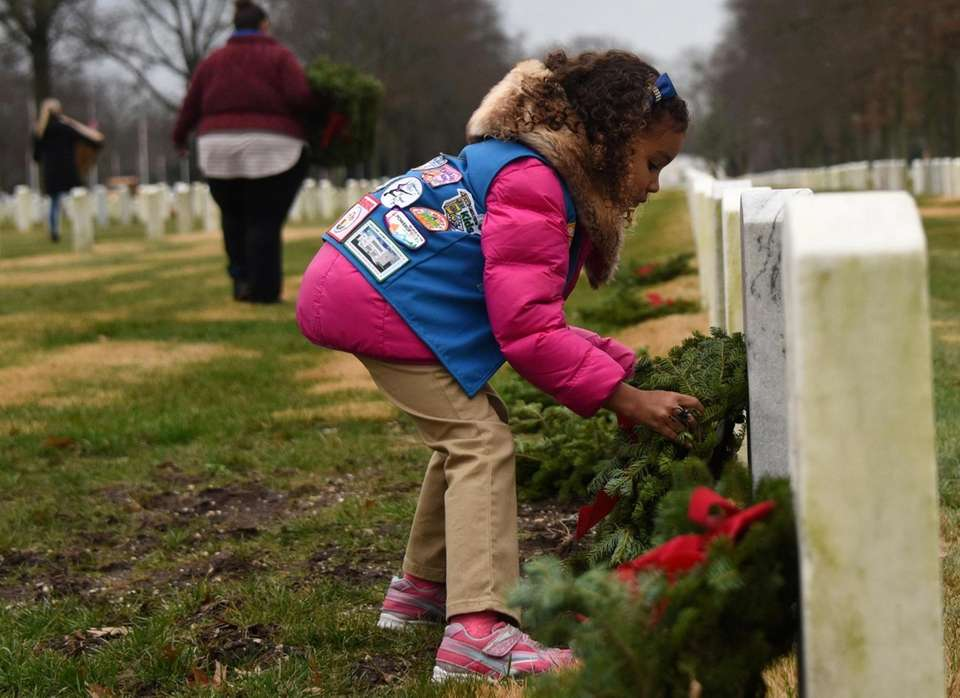 Victoria Vitullo, 6, of Valley Stream, places wreaths