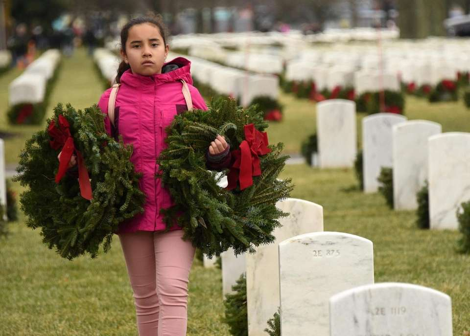 Alexcia Cruz, 11, of Baldwin places wreaths on