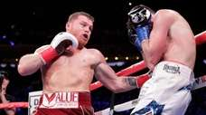 Mexico's Canelo Alvarez, left, punches England's Rocky Fielding