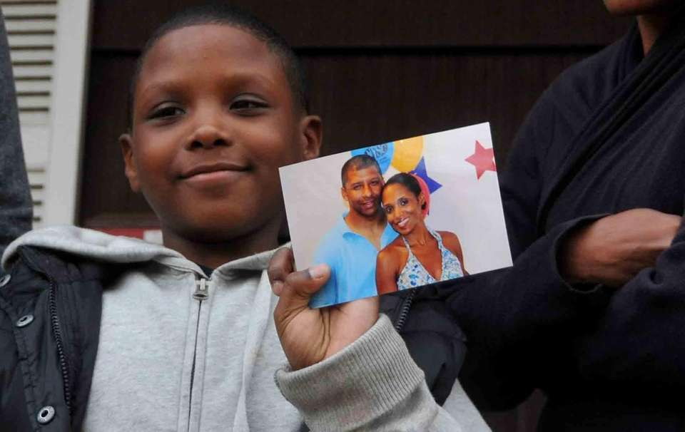 Joshua Menzies, 9, holds a photo of his