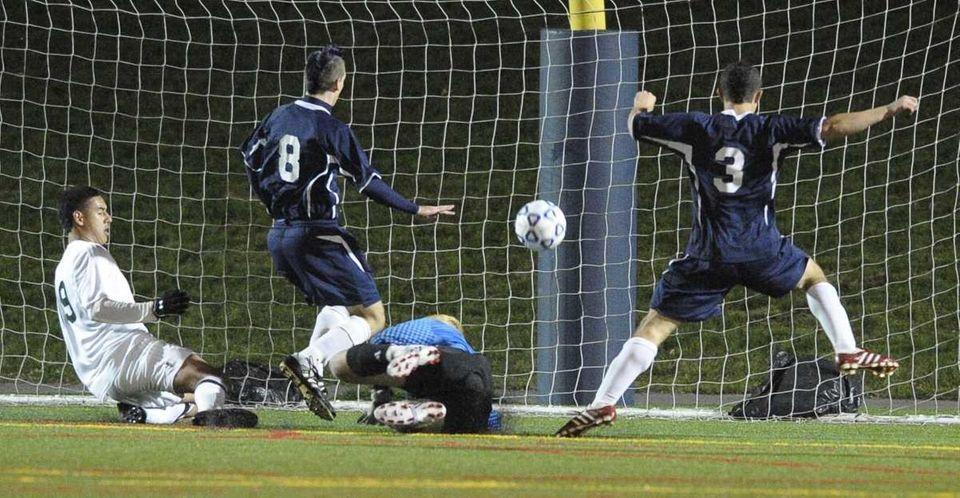Brentwood's Jonathan Interiano, left, scores past Massapequa keeper