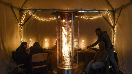 Visitors warm themselves by fire in a tent