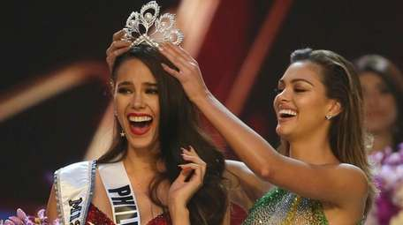 Catriona Gray of the Philippines, left, reacts as