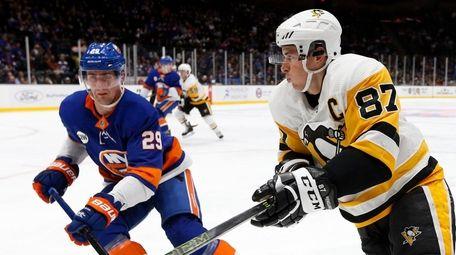 The Penguins' Sidney Crosby skates against the Islanders'