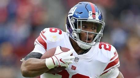 Saquon Barkley of the Giants carries the ball