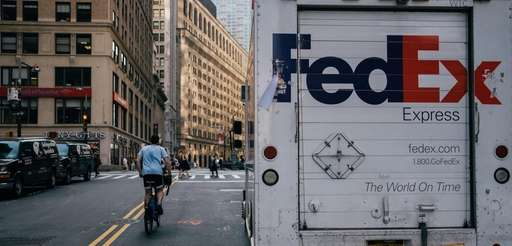 A person rides a bicycle past a FedEx