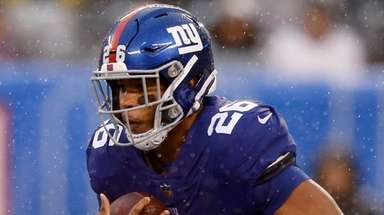The Giants' Saquon Barkley runs the ball during