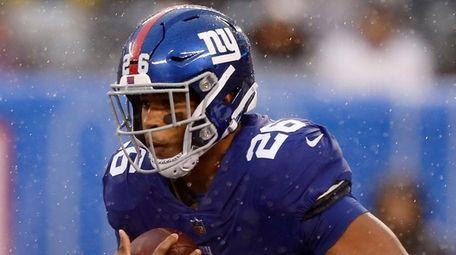 The Giants' Saquon Barkley runs the ball during