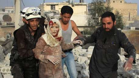 Syrian rescue workers and residents help an injured