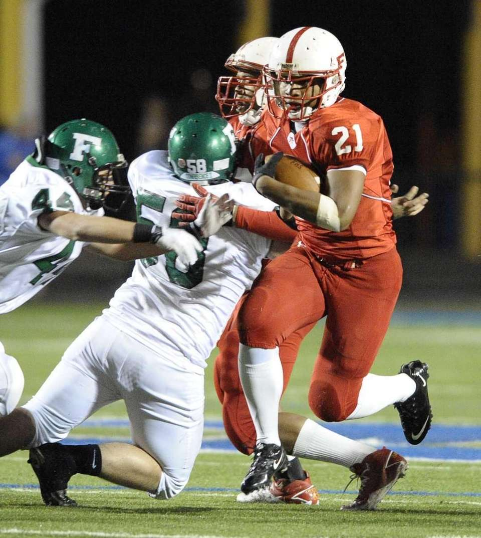 Freeport's Daniel Olivier evades a tackle by Farmingdale