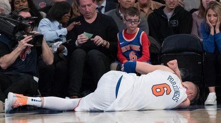 Knicks forward Kristaps Porzingis lies on the ground
