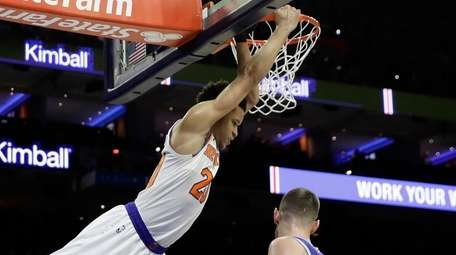 The Knicks' Kevin Knox hangs on the rim