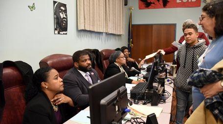 Wyandanch school board president James Crawford, center, speaks