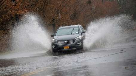 A car navigates a flooded portion of Commercial