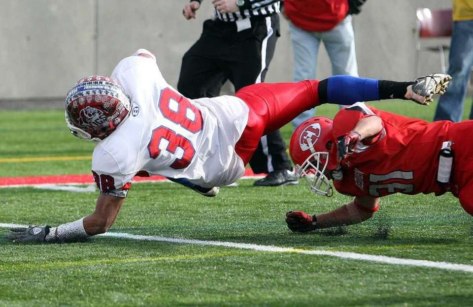 Bellport's Mike Burton (38) dives for the 8