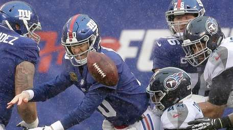 Giants quarterback Eli Manning, left, fumbles the ball