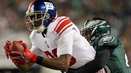 The Giants' Hakeem Nicks tries to break a