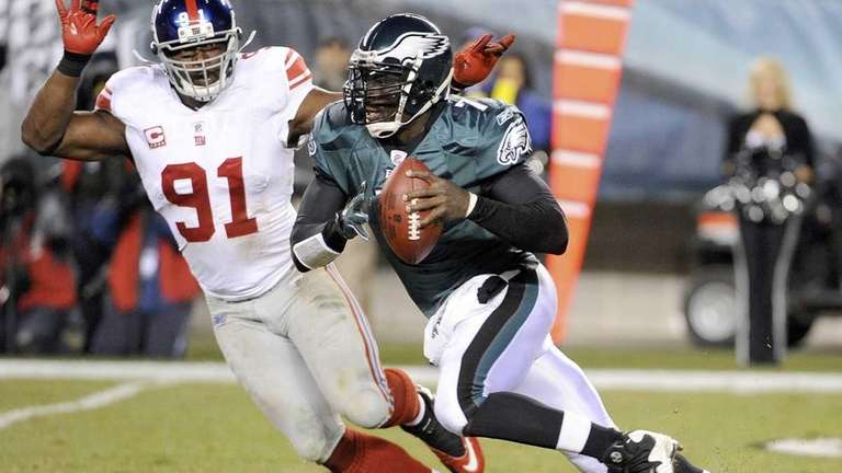 Philadelphia Eagles quarterback Michael Vick scrambles past New