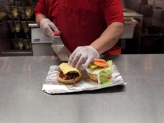 A bacon cheeseburger is assembled at the Five