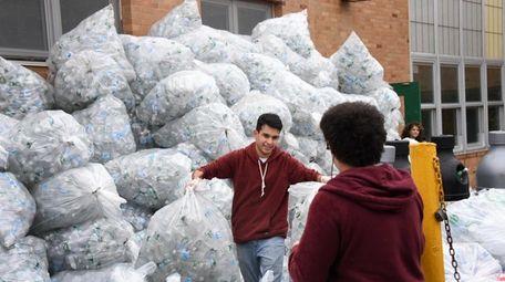 Brentwood High School student Osiel Penera, center, helps
