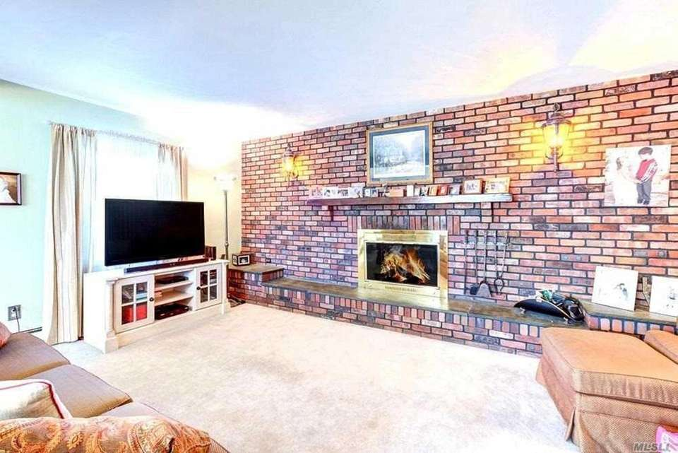 The living room features a full brick wall