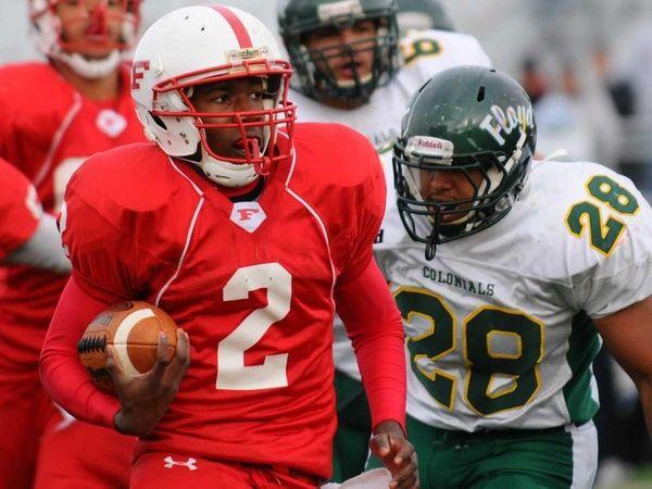 Freeport quarterback Isaiah Barnes, left, looks to evade