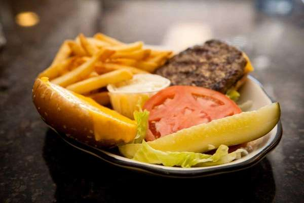 A cheeseburger and side of fries are ready