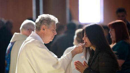 Deacon Vito Taranto gives Communion during Christmas Mass